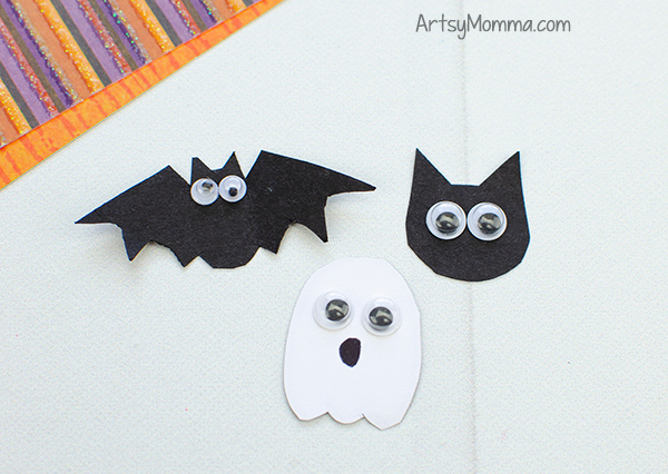 white ghost and a black bat and cat shapes with tiny googly eyes