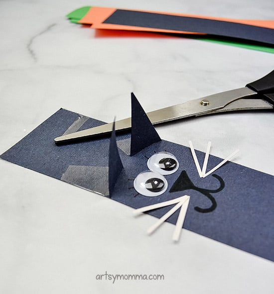 Tape black triangles to the black cat paper strip