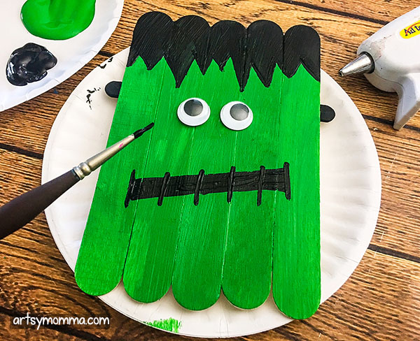 Paint a black stitched mouth on the Jumbo Wood Craft Stick Frankenstein.