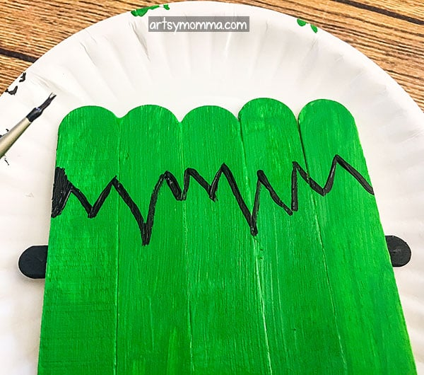 Paint jagged black hair on Frankenstein Halloween Craft