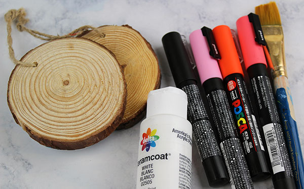 Supplies for wood slice ornaments including paint pens