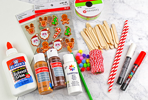 Mini Gingerbread House Craft Supplies: paint, mini popsicle sticks, pom poms, stickers, straws, ribbon