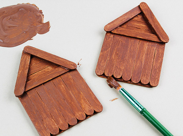 Paint the assembled wood craft sticks brown to create a Gingerbread house