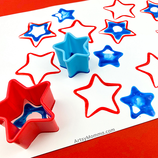red and blue stars stamped on white paper using cookie cutters