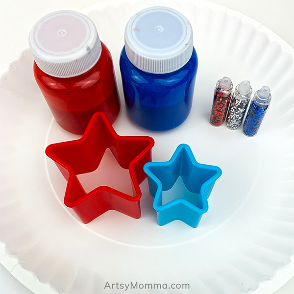 Red and Blue Kids Paint, glitter, star cookie cutters on a paper plate